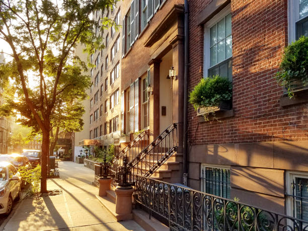 Old brownstone buildings along a quiet neighborhood street in New York City Old brownstone buildings along a quiet neighborhood street in Greenwich Village, New York City NYC soho new york stock pictures, royalty-free photos & images