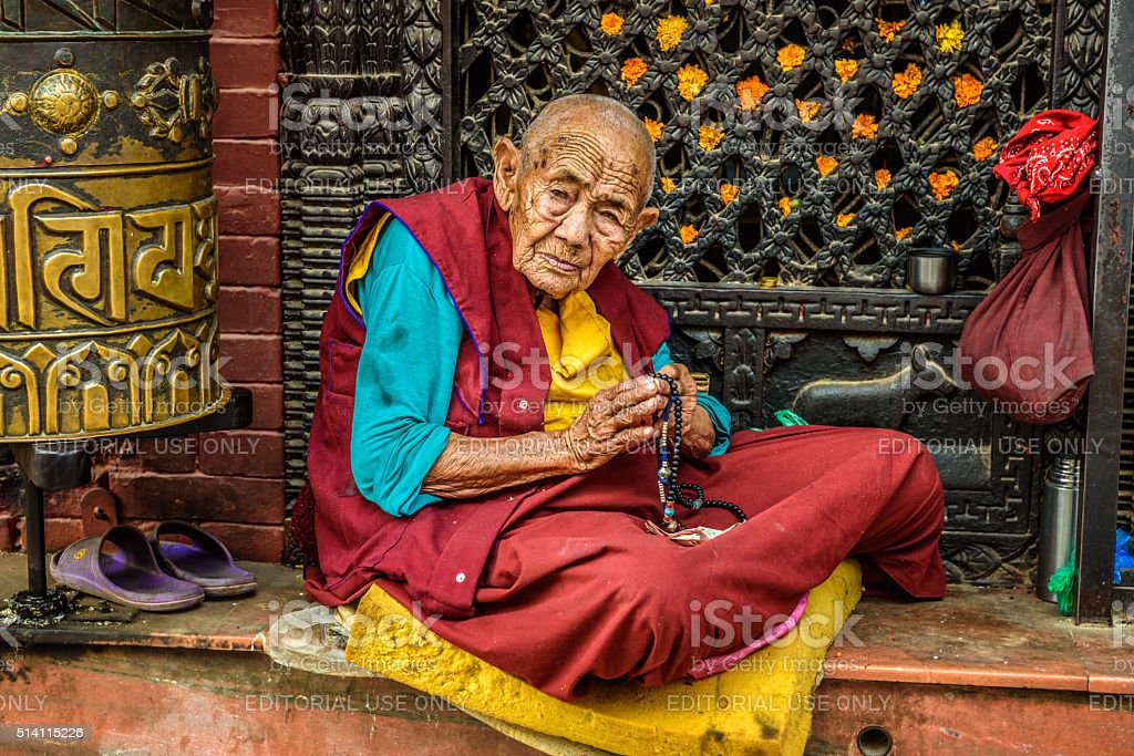 Old buddhist nun begs in Kathmandu, Nepal stock photo