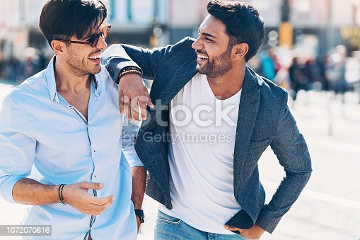 Two smiling young men talking outdoors in the city