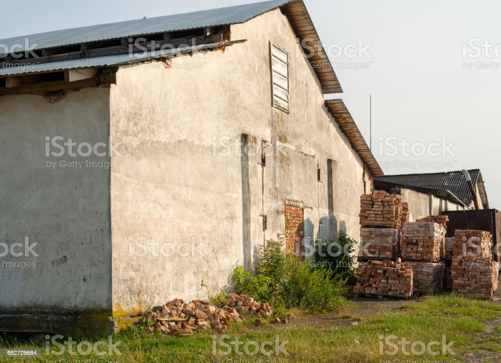 Old building and stacks of bricks nearby stock photo