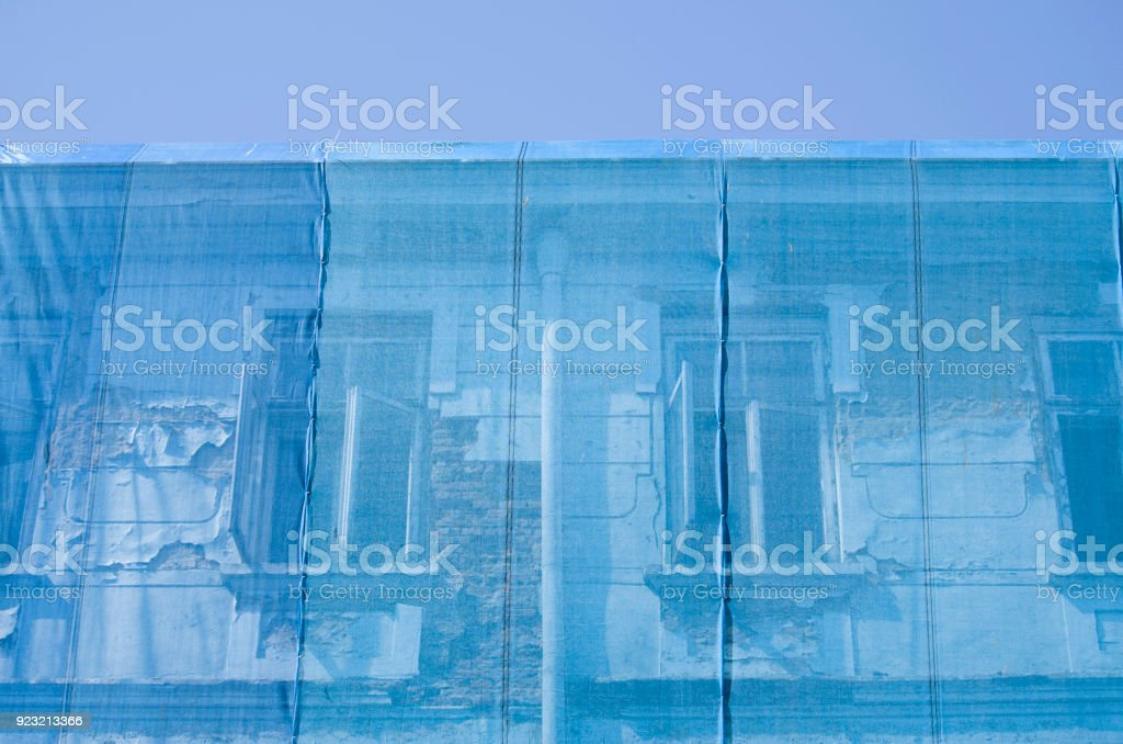 Old building covered with blue safety net stock photo