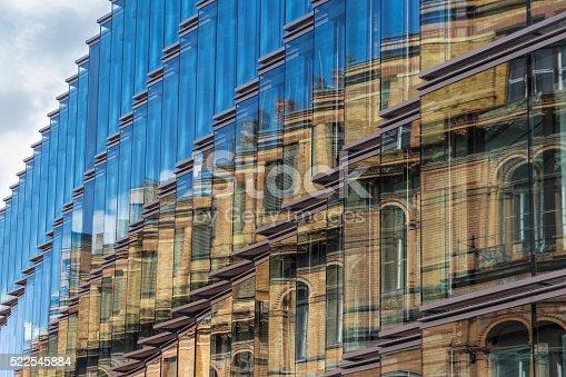 istock old building facade reflection in modern building glass facade 522545884