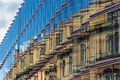 old building facade reflection in modern building glass facade