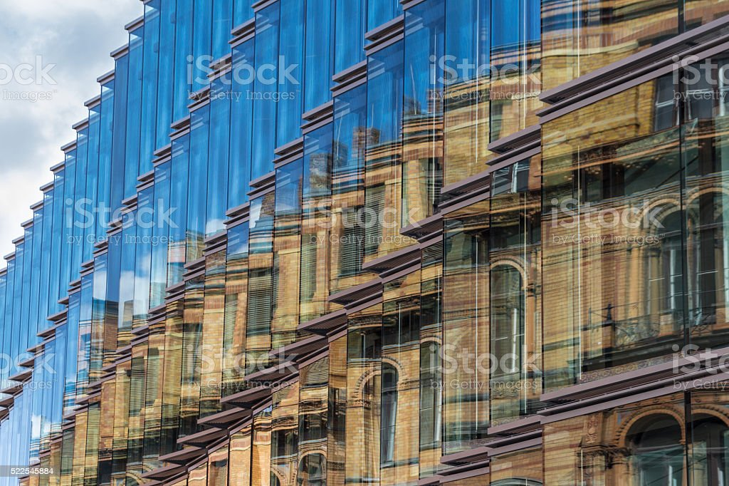 old building facade reflection in modern building glass facade stock photo