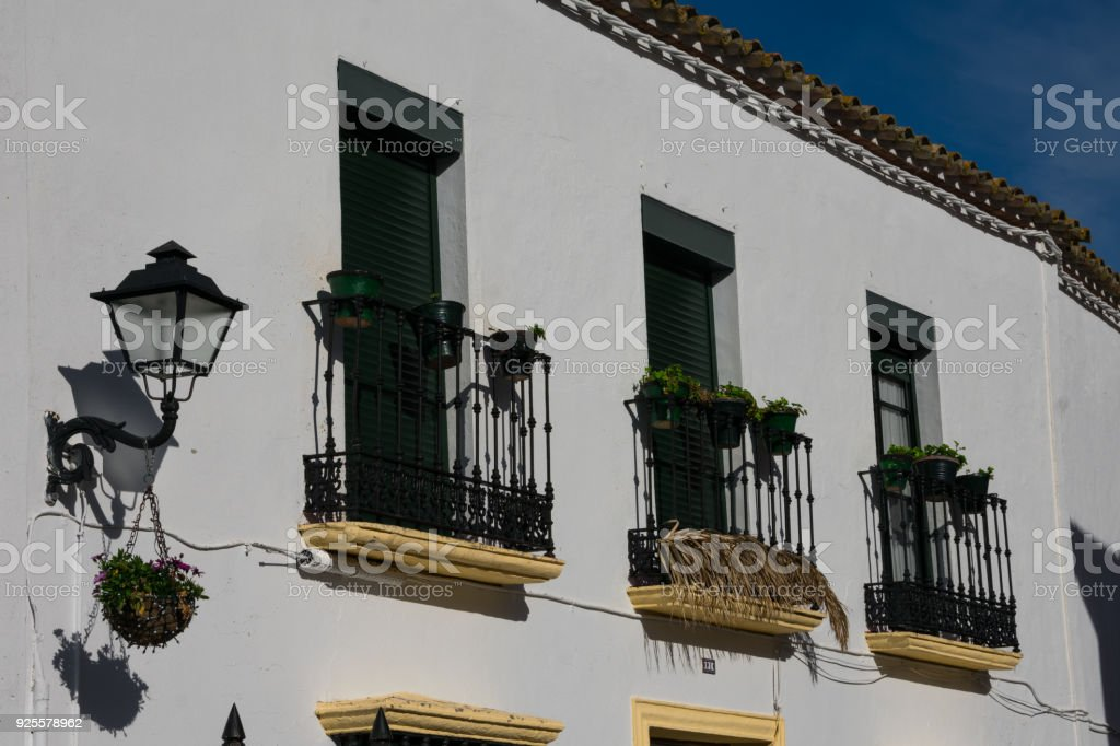 Old building facade with balconies and plant pots stock photo