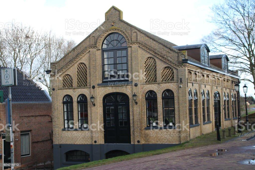 Oude gebouw geweest die gerestaureerd langs de dijk van de Hollandse IJssel, Capelle aan den IJssel, Nederland foto