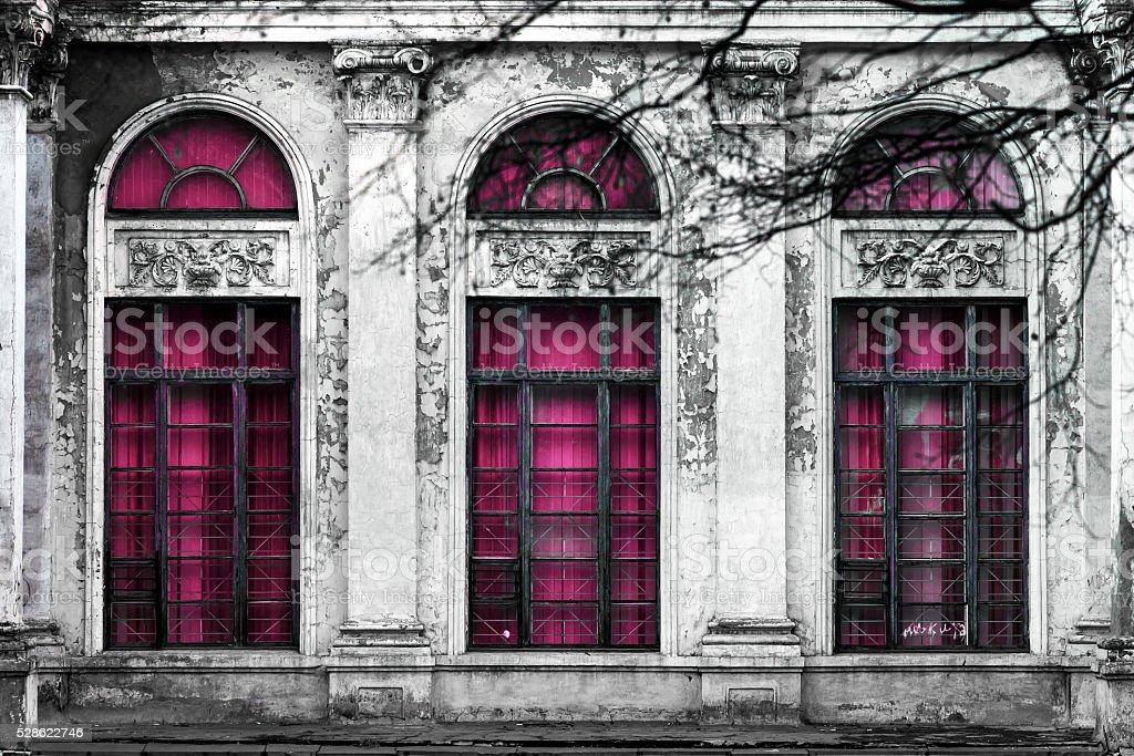 antiguo edificio con tres grandes ventanas de vidrio abovedado dan su toque de color rosa. - foto de stock