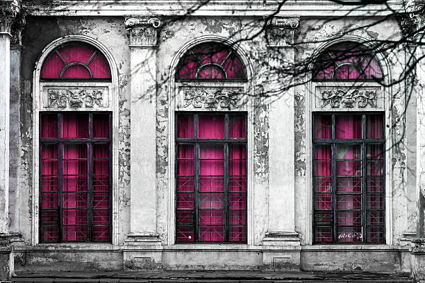 old  building with three large arched windows of pink glass. stock photo
