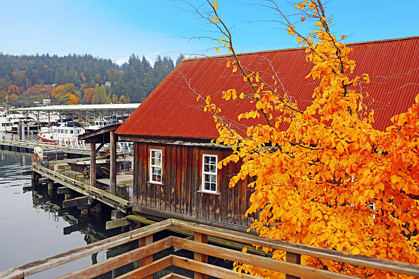 Old building with water front view during fall time Old wooden house with water front view. View of private boats. Gig Harbor. Pacific Northwest. gig harbor stock pictures, royalty-free photos & images