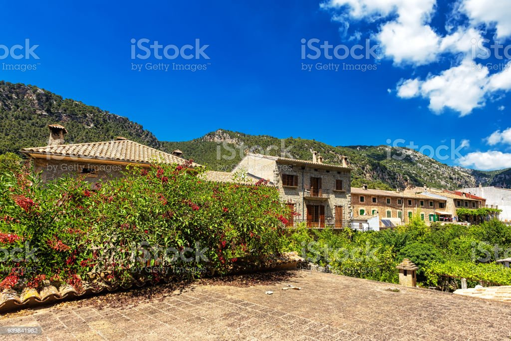 Old buildings, blooming plants and mountains in town Valdemossa, Mallorca stock photo