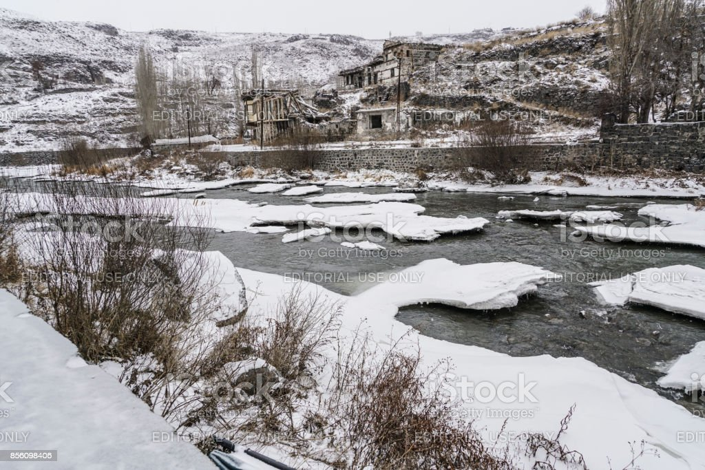 Old buildings by frosted river in Kars,Turkey stock photo