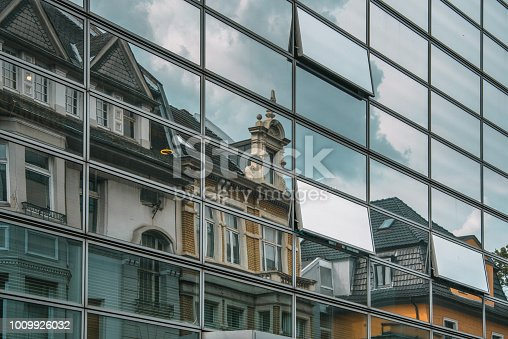 Old buildings reflected on modern facade