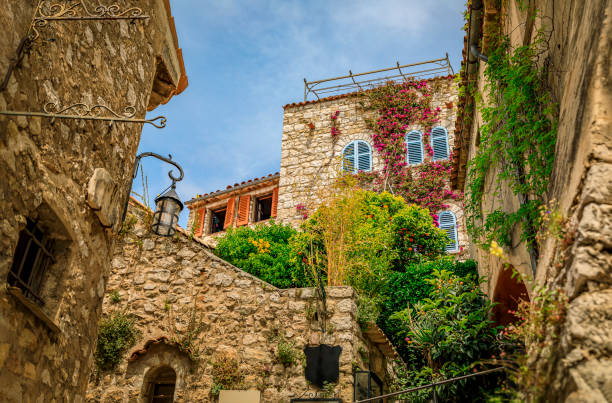 Old buildings with flowers in the streets of Eze Village, medieval city in South of France along the Mediterranean Sea stock photo