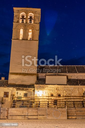 Old bullring in the main square of a town at night next to the church tower
