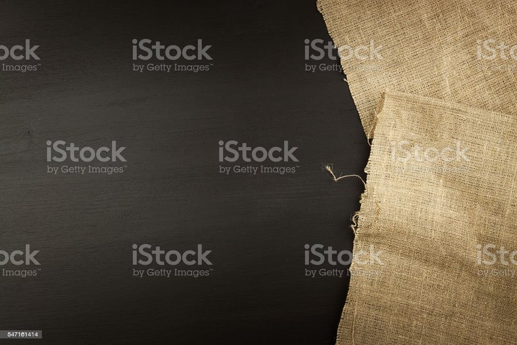 Old burlap on a black wooden board. stock photo