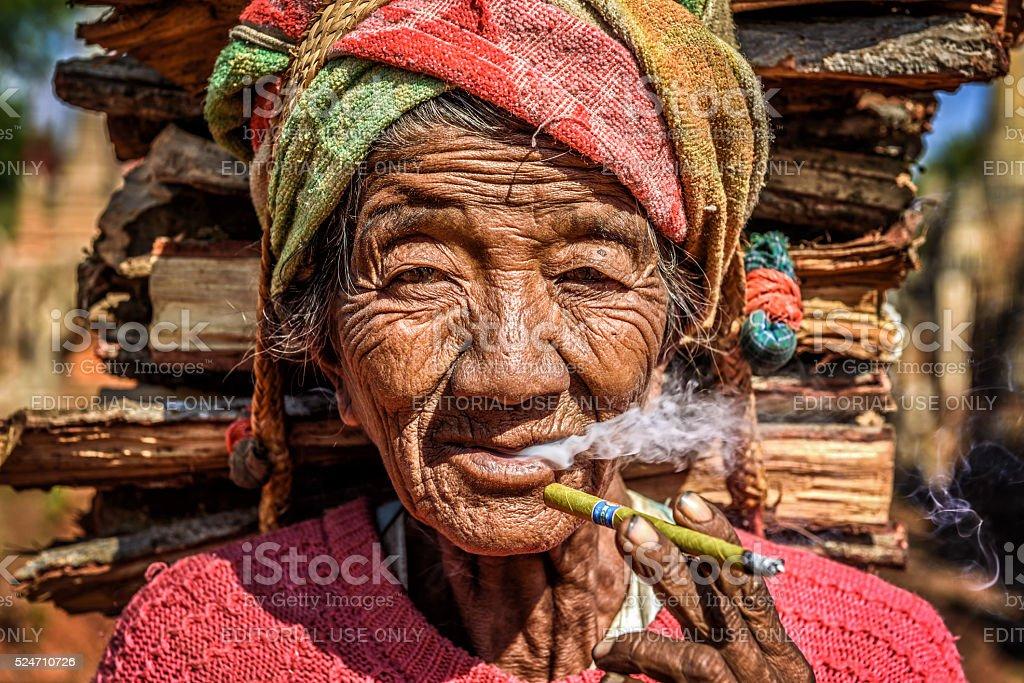 Old burmese woman smoking stock photo