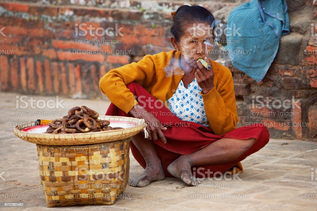 Old Burmese woman with face painting Thanaka cosmetic smoking cigar stock photo