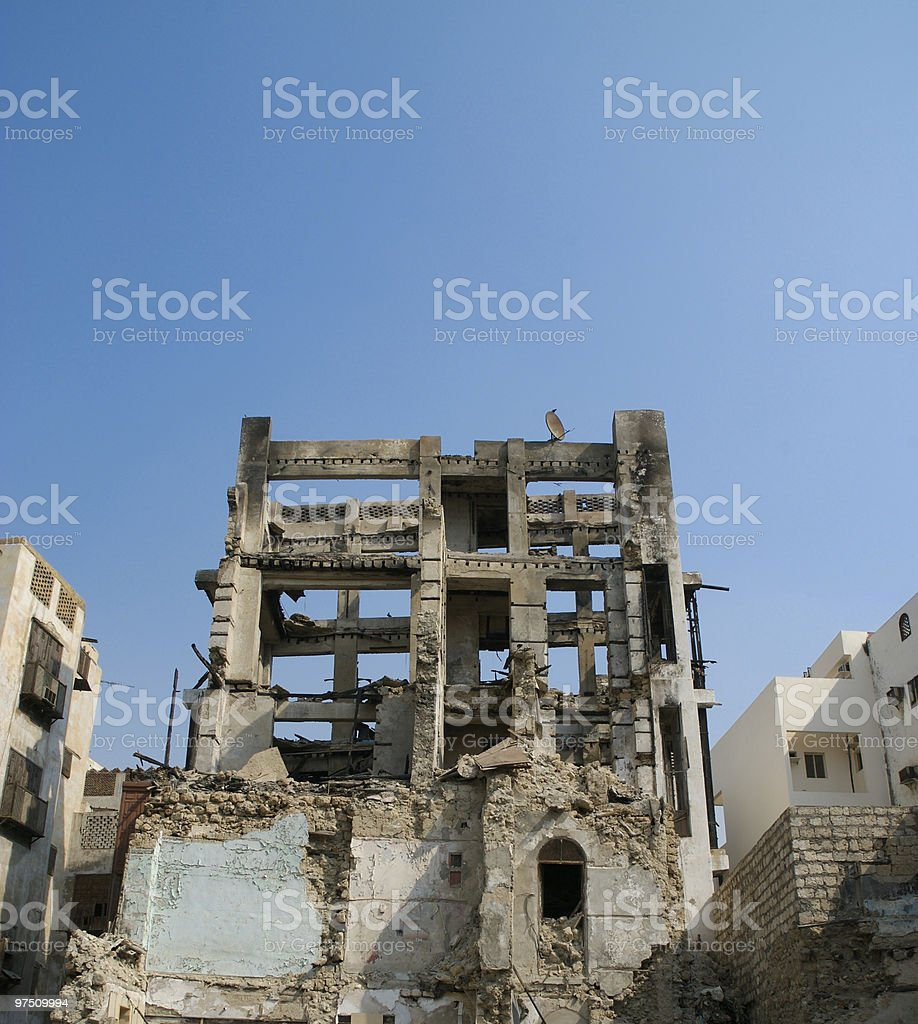 Old burnt and demolished building with satellite dish on top royalty-free stock photo