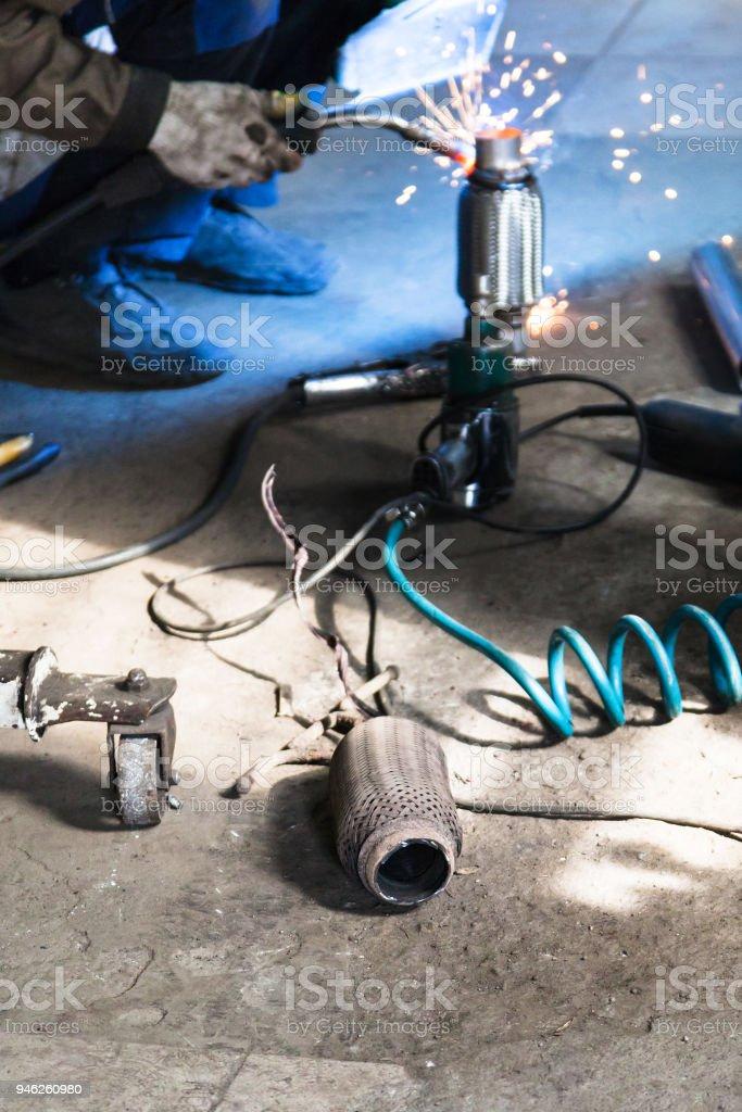 old burnt corrugation muffler on floor of workshop stock photo