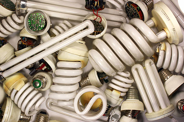 old burnt fluorescent energy saving lamps. - fluorescent light stock pictures, royalty-free photos & images
