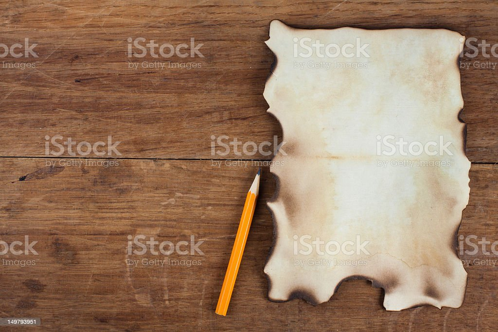 Old Burnt Paper and a Pencil on Wood background royalty-free stock photo