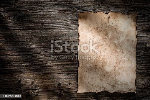 Old burnt parchment posted to a rustic wood background with a pushpin. The parchment is at the right of an horizontal frame. Copy space available either on parchment and wood background. Predominant color is brown. Low key DSRL studio photo taken with Canon EOS 5D Mk II and Canon EF 100mm f/2.8L Macro IS USM.