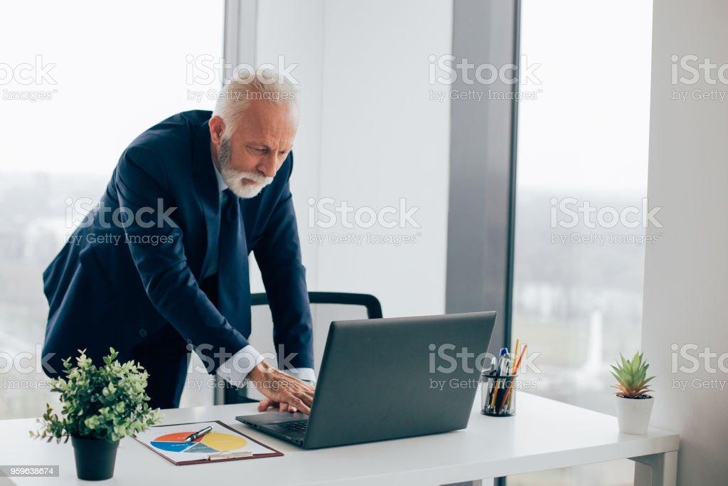 Viejo hombre de negocios de pie y mirando portátil - Foto de stock de Adulto libre de derechos