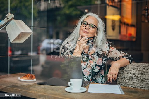 One woman, modern mature business lady sitting in cafe alone, using laptop.