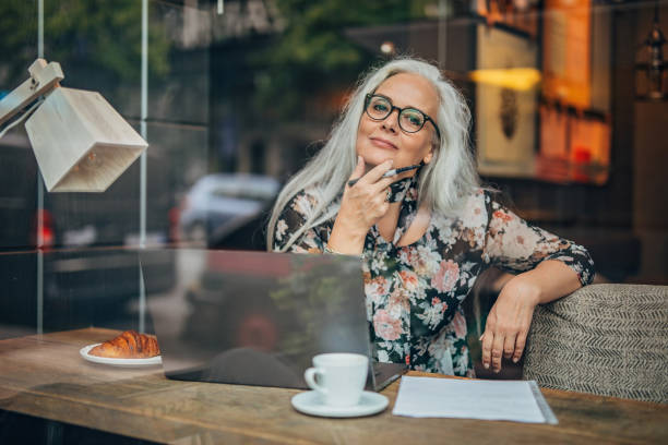 Old business woman sitting in cafe alone