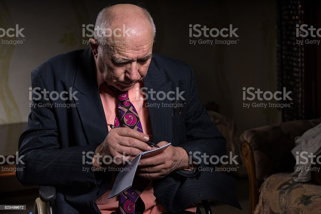 Old Businessman on his Wheelchair Writing Notes stock photo