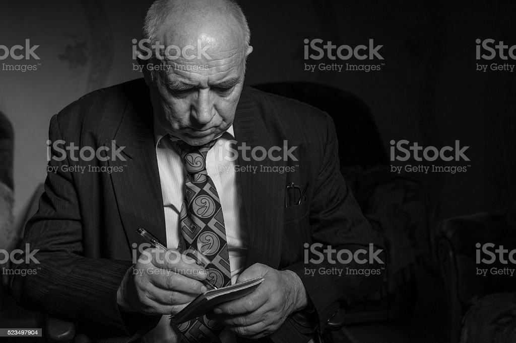 Old Businessman Writing Some Notes in Monochrome stock photo