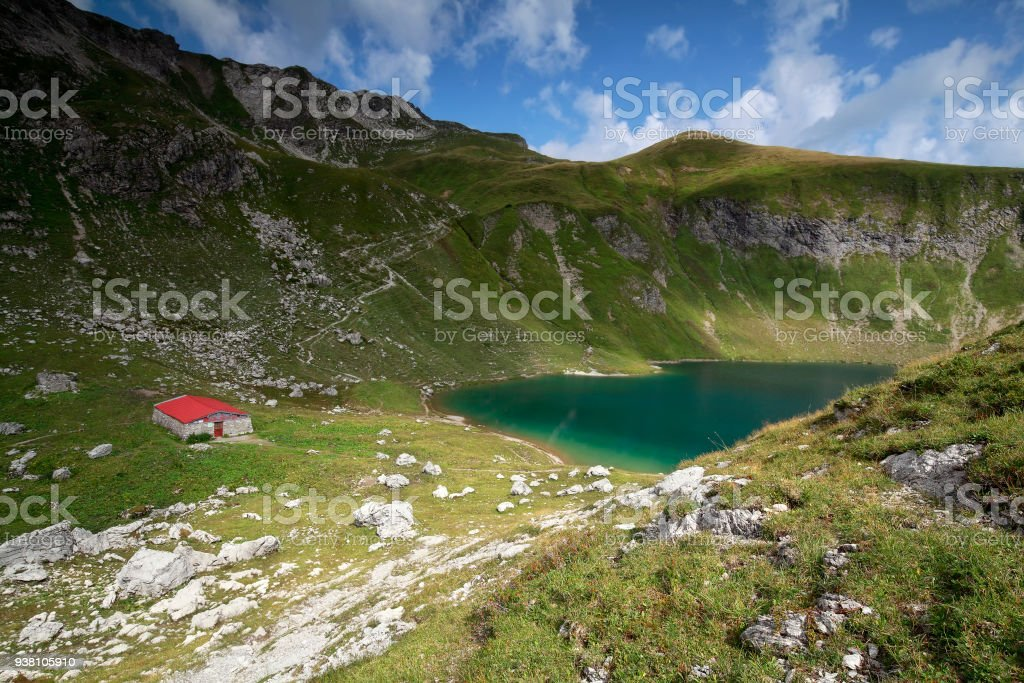 old cabin by alpine turquoise lake in mountains stock photo