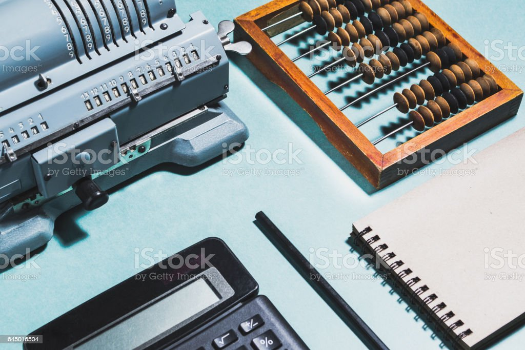 Old calculating machine on a green background. Accounting or business concept stock photo