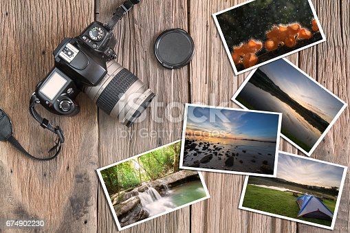 istock Old camera and photos on vintage wooden background 674902230