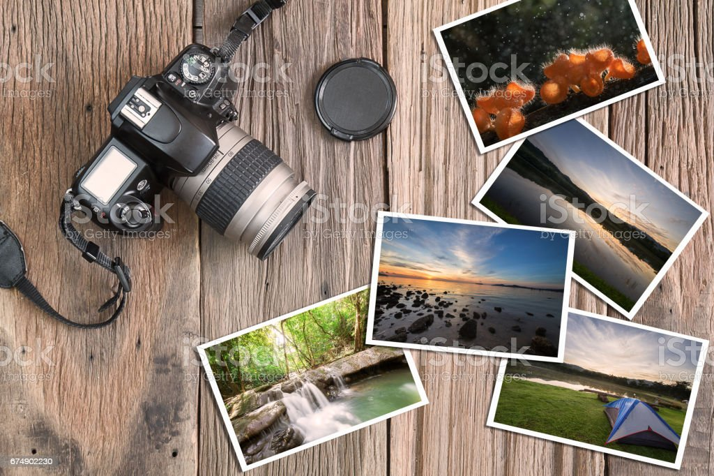 Old camera and photos on vintage wooden background stock photo