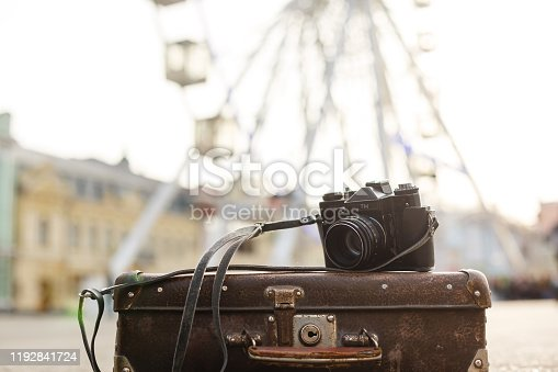 old camera and suitcase against the background of the ferris wheel