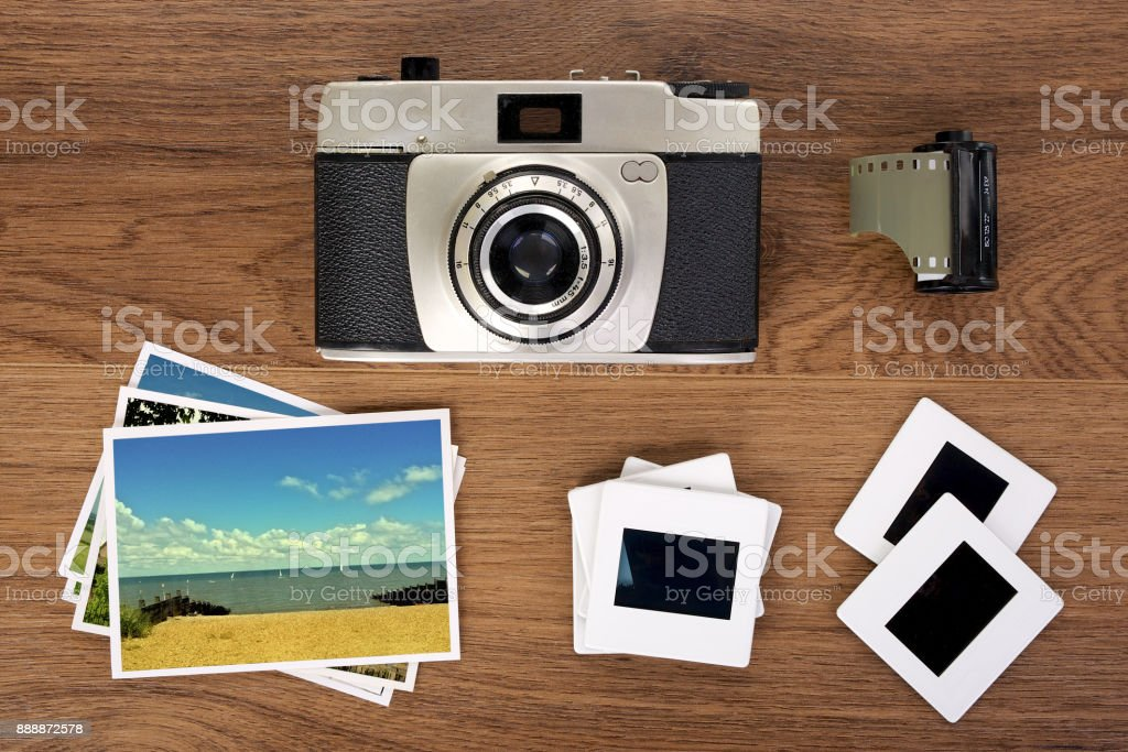 Old camera, mounted film slides and photo's on wooden background stock photo
