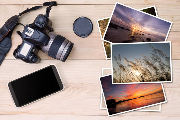 Old camera, smartphone and stack of photos on wooden background stock photo