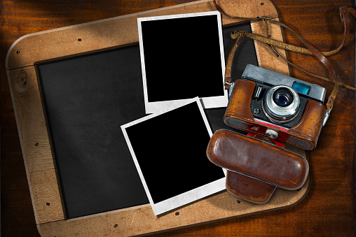 Old Camera with Empty Photos and Blackboard