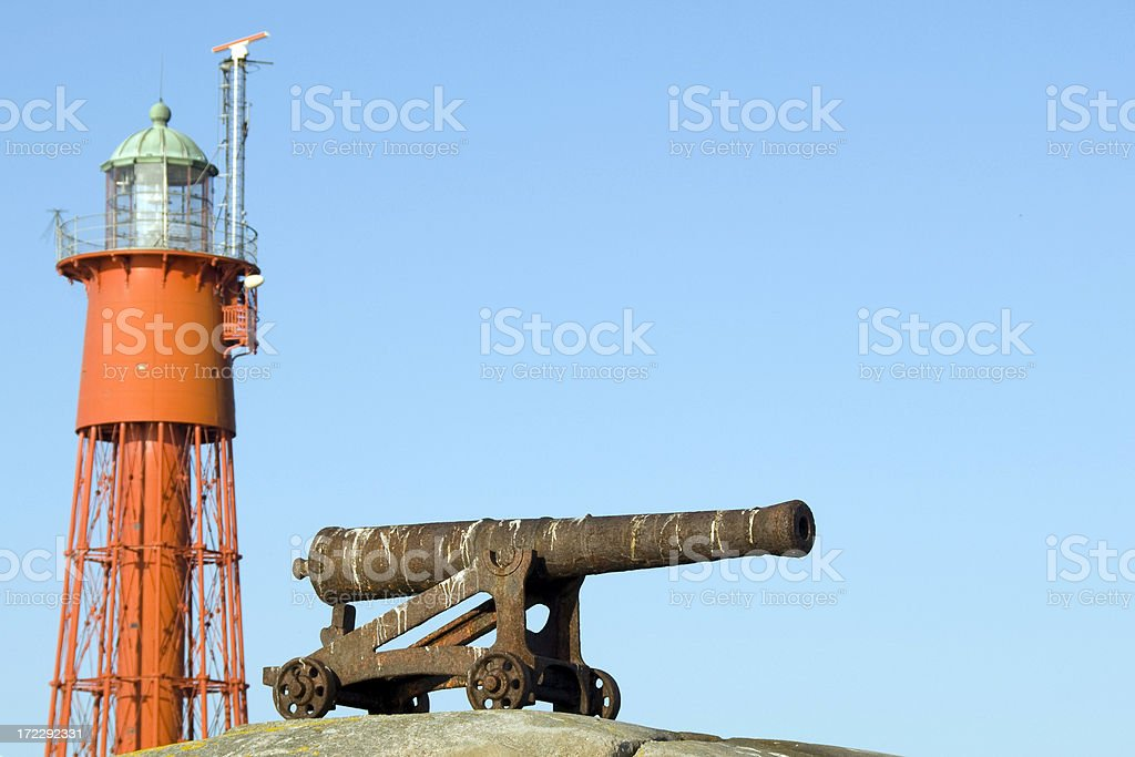 Old cannon and lighthouse stock photo
