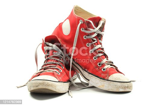 Old and dirty red canvas sneakers, isolated over white