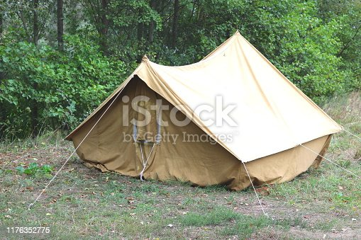 Old canvas tent in tourist camp in summer on background of trees
