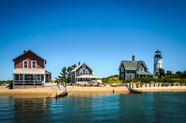 Old Cape Cod Cottages The 19th century cottage colony and lighthouse at the end of Sandy Neck peninsula in Barnstable Harbor on Cape Cod, Massachusetts has no electricity nor water. cape cod stock pictures, royalty-free photos & images