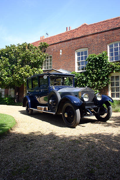 Old Car and Farmhouse An old Rolls Royce parked in front of a farmhouse manor. royce lake stock pictures, royalty-free photos & images