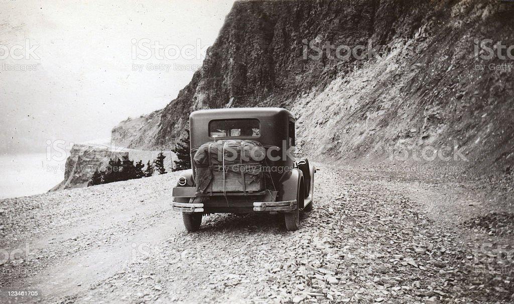 Old car driving to Logan Pass, Glacier Park royalty-free stock photo