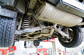 Old car on the lift in the service center against blurred background. View of the rear suspension of the car.