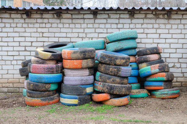Old car painted tires. Many colorful tires against a white brick wall. Outside Without anyone sopaatervinning stock pictures, royalty-free photos & images