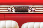 Old car radio inside a red classic American car with chrome dashboard