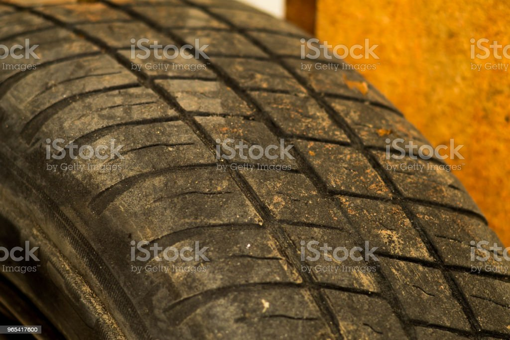 Old car tire tread texture background. Worn out protector of car tire. Used wheels close up. royalty-free stock photo