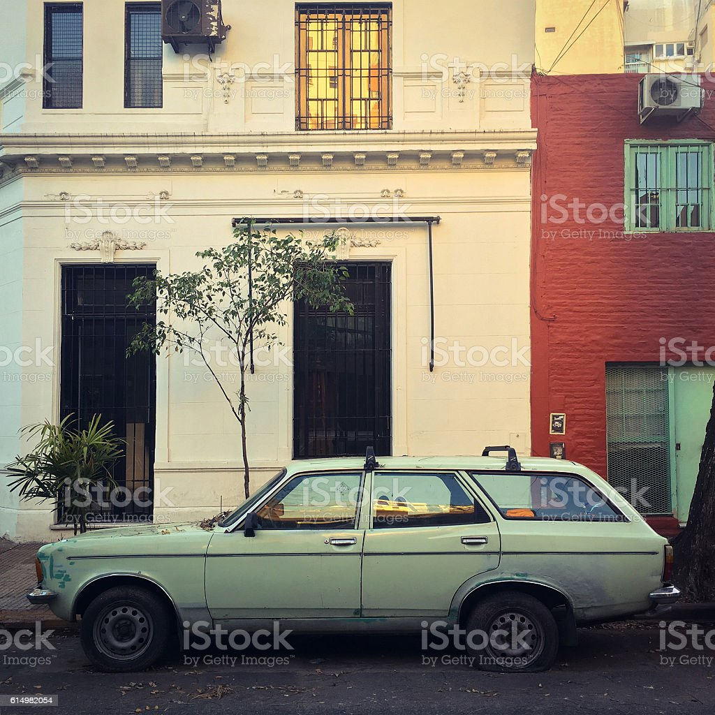 Old car with flat tire in the street stock photo